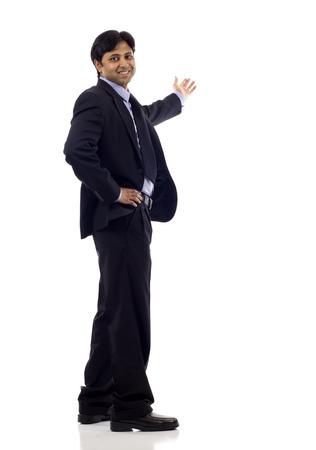 alzando la mano: De cuerpo entero de un feliz hombre de negocios indio presenta y que muestra con copia espacio para el texto aislado en el fondo blanco Foto de archivo