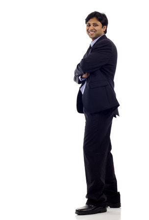 length: Full length of a confident Indian business man with hands folded isolated over white background