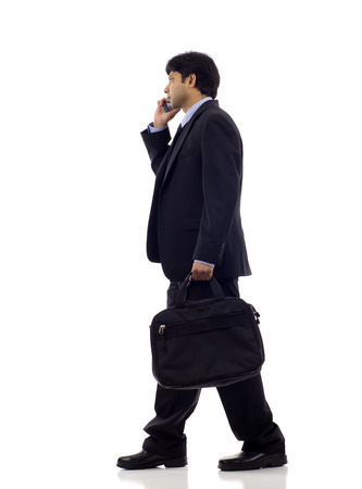 Side view of an Indian business man talking on the mobile phone isolated over white background photo