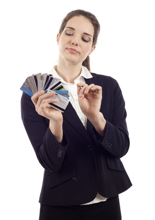 creditcards: Beautiful young woman choosing which credit card to pay with, isolated over white