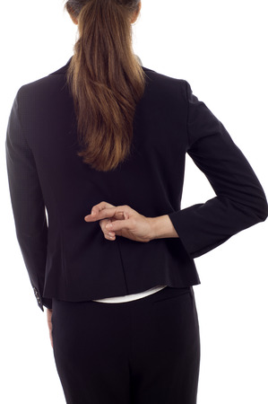 Closeup of a businesswoman with crossed fingers behind her back isolated over white background