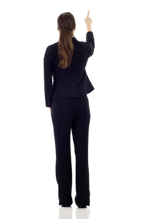 only 1 woman: Full body of young business woman pointing at something in her back, isolated on white background Stock Photo