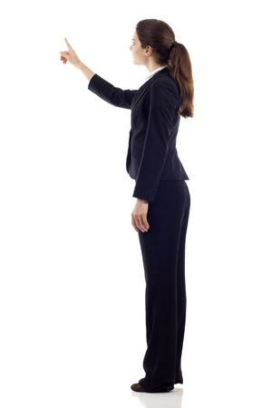 Full body of young business woman pointing at something from the back, isolated over white background
