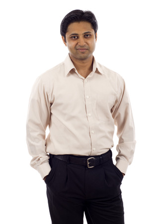 cocky: Confident young Indian businessman with hands in pockets isolated over white background