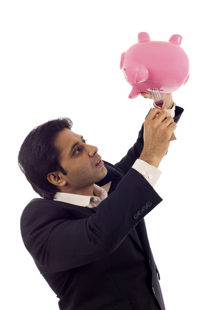 withdraw: Desperate Indian businessman trying to take money out of a piggybank with a fork isolated over white background