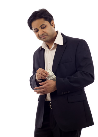 Indian Businessman pulling, hiding money from his sleeve isolated over white background photo