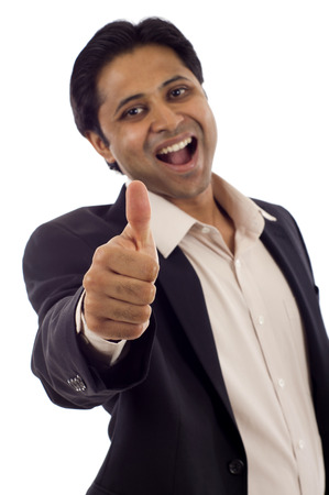 Happy young Indian businessman showing thumbs up sign isolated over white background