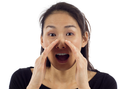 chatty: Young Asian woman loud screaming or calling out to someone isolated over white background Stock Photo