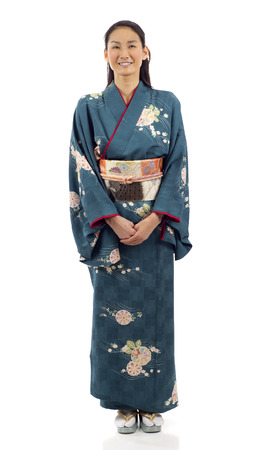 traditional culture: Full length of a smiling Japanese kimono woman standing isolated over white background