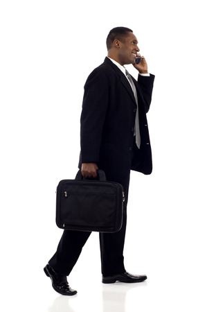 Happy black businessman talking on mobile phone while walking isolated white background