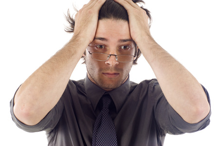 Stressed man with his hands on his head as if he had a headache - isolated over a white background