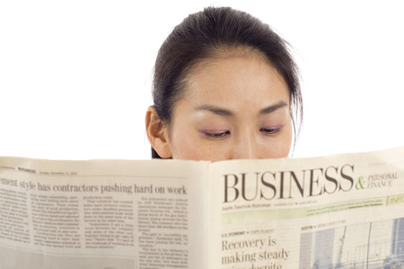 Closeup of an Asian woman reading a business newspaper isolated over white background photo