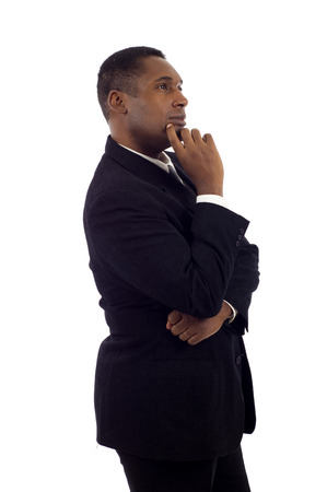 Blackc businessman standing on white background, looking off into distance