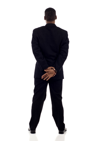 Full length of an African American business man standing, hands together back view isolated over white