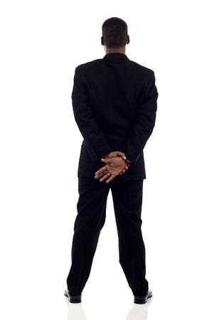 persons back: Longitud total de un afroamericano hombre de negocios de pie, con las manos juntas vista posterior aislado más de blanco Foto de archivo