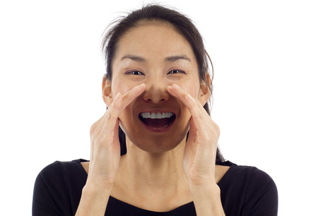 chatty: Happy young Asian woman loud screaming or calling out to someone isolated over white background Stock Photo