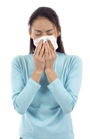 winter woman: Flu or cold - sneezing woman sick blowing nose isolated over white background