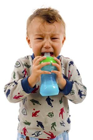 fussy: Baby Boy has Stopped Crying, and Started to Drink his Milk Bottle- Isolated over a White Background