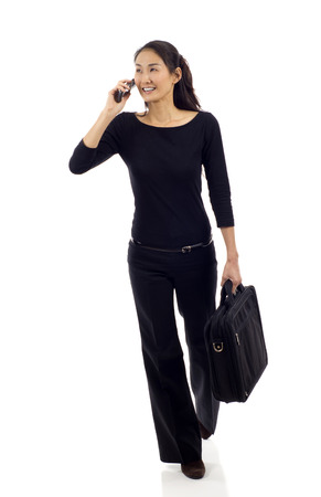 chinese people: Asian businesswoman walking while talking on mobile phone isolated over white background