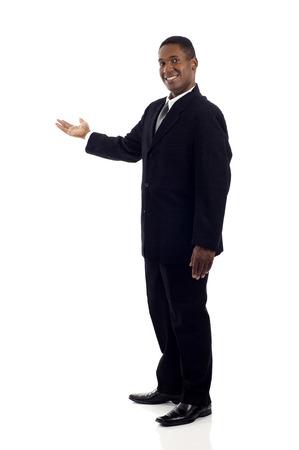 persona de pie: De cuerpo entero de un feliz hombre de negocios negro presenta y que muestra con copia espacio para el texto aislado en el fondo blanco