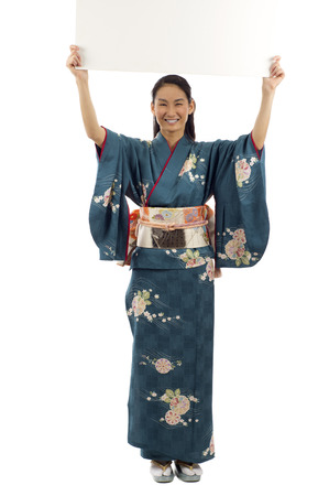 foreign bodies: Full length of smiling Japanese kimono woman holding a blank billboard with copy space for text isolated over white background