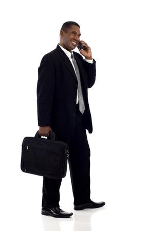 gente adulta: Hombre de negocios negro feliz hablando por teléfono móvil mientras caminando aislados sobre fondo blanco