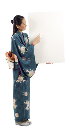 Full length of Japanese kimono woman holding a blank billboard with copy space for text isolated over white background Stock Photo