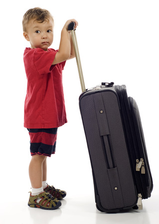 Little boy with luggage, ready to travel