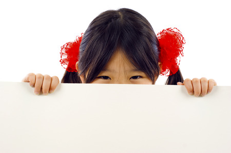 young add: Friendly little Asian girl behind a banner add isolated over a white background