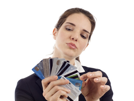 Business woman choosing which credit card to pay with, isolated over white Foto de archivo