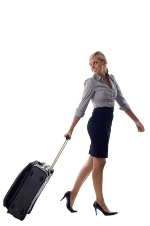 Full length of a smiling business woman with luggage looking back at copyspace, isolated over a white background photo