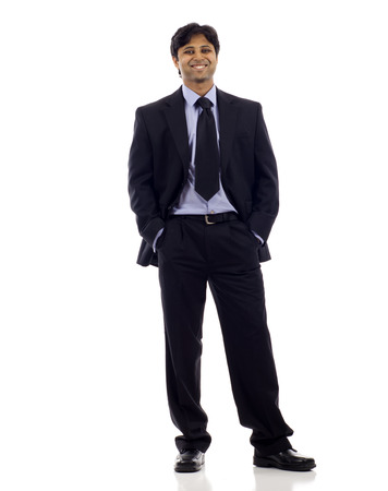 Full length of a  happy Indian business man standing with hands in pocket isolated over white background. Studio shot.