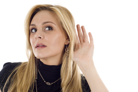 bruit: Businesswoman leans toward the right copyspace showing that she is listening for something.