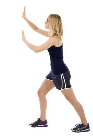 Fitness girl pushing something isolated over white background