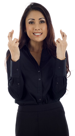 hoping: Young Asian business woman hoping for something with fingers crossed against white background Stock Photo