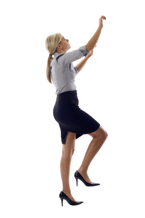 Blond business woman climbing a ladder  isolated over a white background