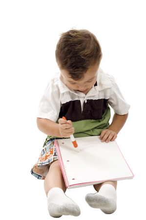 Cute child drawing with color pen on a blank notebook isolated over white Stock Photo
