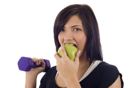 eat right: Attractive woman  holding a dumbbell and eating an apple - Eat right and exercise, Isolated over a white background