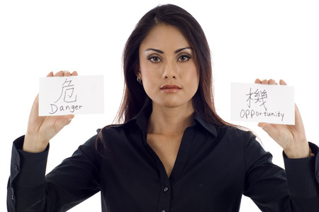 danger: Business Investment Concept: Danger & Opportunity.  Asian businesswoman holding 2 cards, put it together,  it means  Crisis  in Chinese. Stock Photo