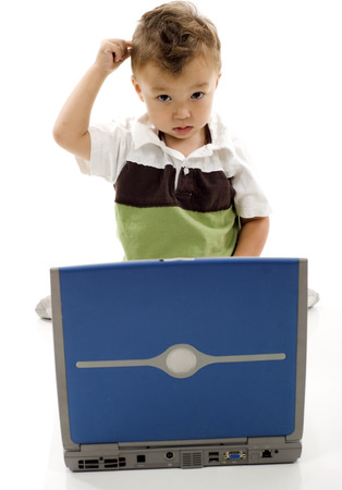 problem: Little boy scratching his head, having problem with his computer - need help! Stock Photo