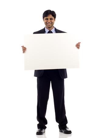 白い背景に分離された空白記号 copyspace を保持している幸せな若いインドのビジネスマンの全長