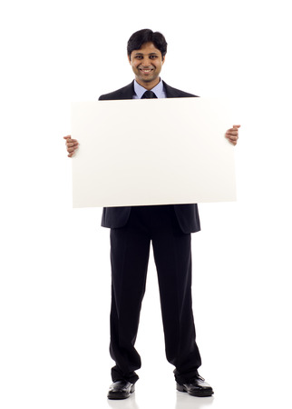 a placard: Full length of a happy young Indian businessman holding blank sign- copyspace isolated over white background