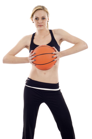 An athletic girl holding a basketball  - isolated over a white background