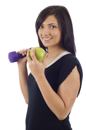 eat right: Attractive woman holding a dumbbell and a green apple - Eat right and exercise, Isolated over a white background