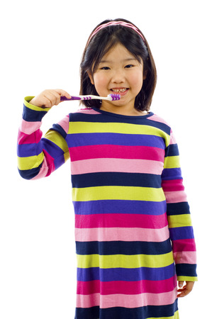 Cute little Asian girl brushing her teeth isolated over white Stock Photo