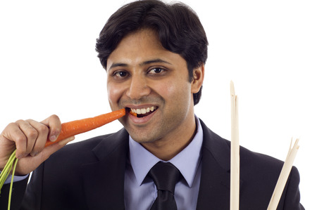 punishment: Business Concept:   Rewards and  Punishment, Young Indian business man eating a carrot and holding broken sticks isolated over white background