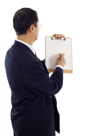 Isolated studio shot of the back view of mature Asian businessman writing on a clipboard Stock Photo
