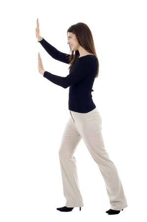Woman pushing an imaginary object isolated over a white background