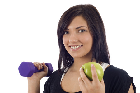 eat right: Young woman holding a dumbbell and a green apple - Eat right and exercise, Isolated over a white background
