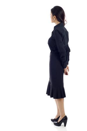 Femme d'affaires d'Asie de l'arrière - regarder quelque chose sur un fond blanc